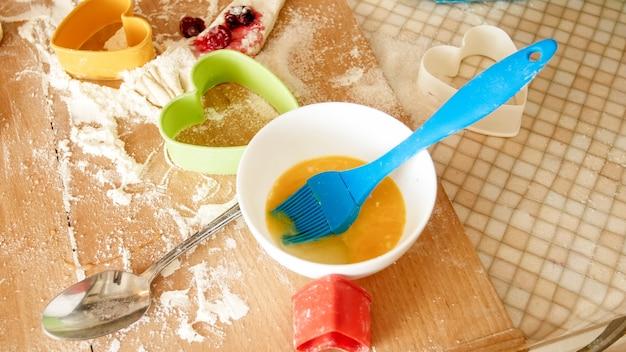 Zbliżenie świeżego ciasta, jajek, mleka i wielu narzędzi do piekarni i gotowania leżącego na dużym drewnianym blacie kuchennym