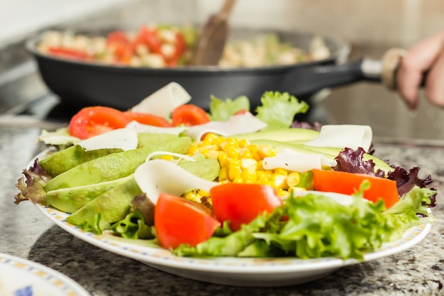 Zbliżenie świeżego naczynia sałatkowego i kobiecego gotowania w czarnej patelni w tle