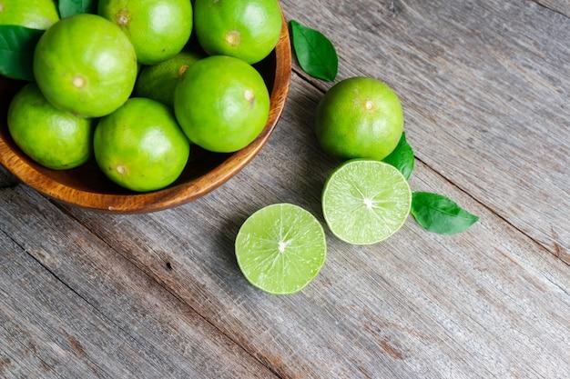Zbliżenie świeżych cytryn cytrusowych limonki na podłoże drewniane.