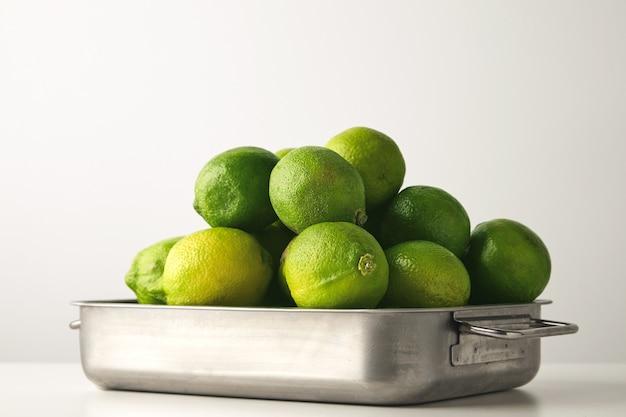 Zbliżenie świeżych limonek w stalowym rondlu na białym tle na białym stole.