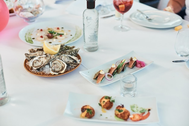 Zbliżenie świeżych ostryg z cytryną na stole restauracji.