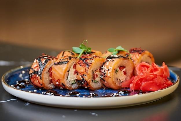 Zbliżenie świeżych rolek sushi z łososiem, serem philadelphia i tuńczykiem na niebieskim talerzu ceramicznym z sosem, sezamem, imbirem i wasabi. stół z czarnego kamienia.