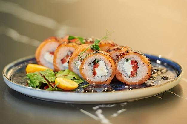 Zbliżenie świeżych rolek sushi z łososiem, serem philadelphia i tuńczykiem na niebieskim talerzu ceramicznym z sosem, sezamem, płatkami kumkwatu i liśćmi. stół z czarnego kamienia.