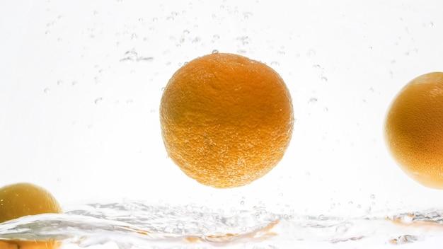 Zbliżenie świeżych soczystych pomarańczy wpadających do wody