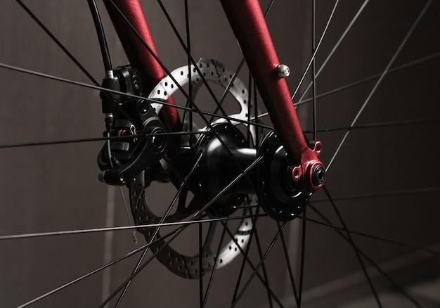 Zbliżenie systemu hamulców tarczowych na czerwonym rowerze szosowym.