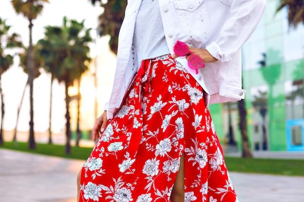 Zbliżenie szczegółów mody, kobieta ubrana w spódnicę maxi z nadrukiem, białą, luźną kurtkę i trzymająca neonowe okulary przeciwsłoneczne, pozująca na barcelonie