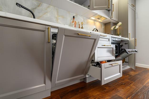 Zbliżenie szczegółów szarej i białej nowoczesnej kuchni klasycznej ze wszystkimi drzwiami są otwarte