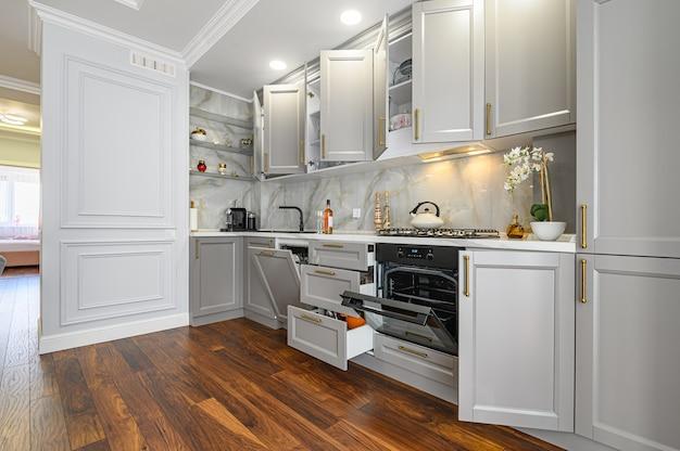 Zbliżenie szczegółów szarej i białej współczesnej klasycznej kuchni zaprojektowanej w nowoczesnym stylu, wszystkie drzwi i szuflady mebli są otwarte