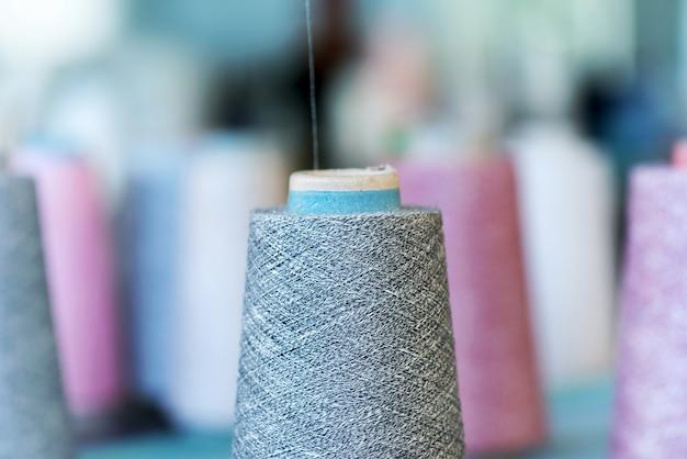 Zbliżenie szczegółów wełny kaszmirowej na stożkowej szpuli w fabryce dzianin z boczną przestrzenią w koncepcji produkcji mody