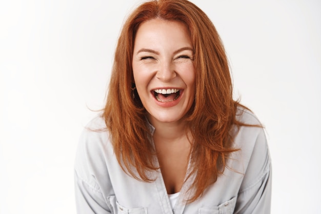 Zbliżenie szczera beztroska radosna ruda dojrzała kobieta ciesz się rodzinnymi letnimi wakacjami śmiejąc się głośno uśmiechnięty uśmiech ząbkowany oczyma nieostrożne starzenie się akceptuję własne zmarszczki wyglądają świeżo optymistycznie
