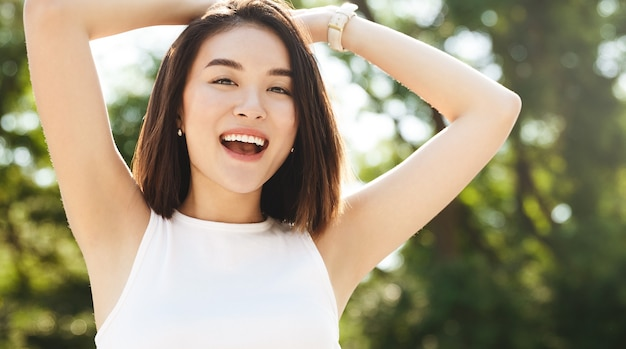 Zbliżenie: szczęśliwa azjatycka kobieta pozuje w parku, uśmiechając się i patrząc na kamery, trzymając ręce za głowę zrelaksowany