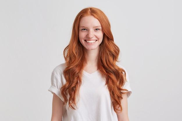 Zbliżenie szczęśliwa całkiem ruda młoda kobieta z długimi falującymi włosami