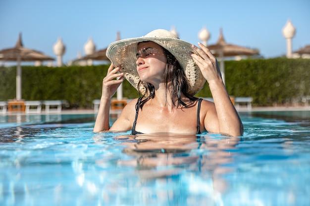 Zbliżenie: szczęśliwa dziewczyna w słomkowym kapeluszu kąpie się w basenie przy słonecznej pogodzie. koncepcja wakacji i ośrodka.