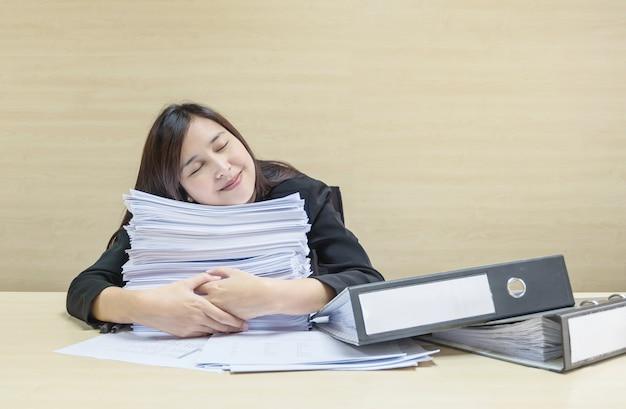 Zbliżenie szczęśliwa kobieta pracująca śpi po tym, jak zakończy pracę z papieru roboczego