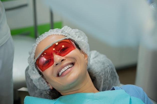 Zbliżenie szczęśliwa młoda kobieta z pięknym uśmiechem po zabiegu wybielania zębów. biała koncepcja leczenia