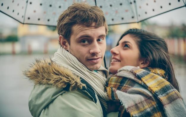 Zbliżenie szczęśliwa młoda para, obejmując pod parasolem w jesienny deszczowy dzień. koncepcja relacji miłości i para.