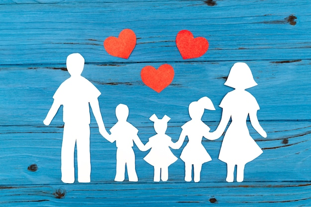 Zbliżenie szczęśliwa papierowa rodzina na błękitnym tle