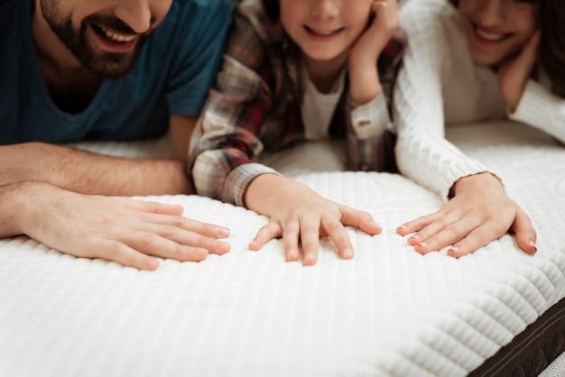 Zbliżenie szczęśliwa rodzina dotyka materaca w sklepie