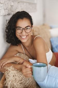 Zbliżenie szczęśliwa zdrowa młoda kobieta z ciemnymi kręconymi włosami, leżąc w wygodnej kanapie na tarasie