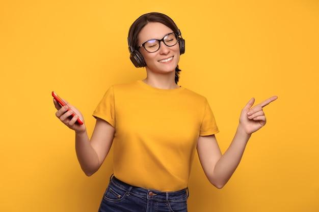Zbliżenie szczęśliwa zrelaksowana kobieta słuchając jej ulubionej listy odtwarzania, ciesząc się piosenkami z bezprzewodowymi słuchawkami