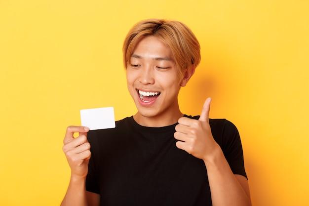 Zbliżenie szczęśliwego i zadowolonego azjatyckiego przystojnego faceta, pokazującego kartę kredytową i kciuki w górę z aprobatą, uśmiechnięty zdumiony, stojący żółtą ścianę