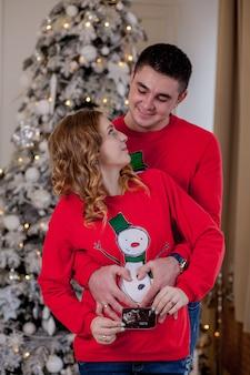 Zbliżenie szczęśliwego małżeństwa klejenia obok choinki. najlepszy prezent na boże narodzenie
