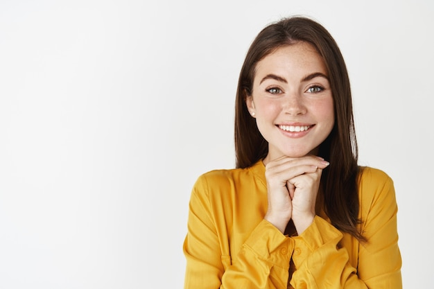 Zbliżenie szczęśliwej i marzycielskiej dziewczyny patrzącej na kamerę z podziwem, opartej na rękach i słuchającej z zainteresowaniem, stojącej nad białą ścianą