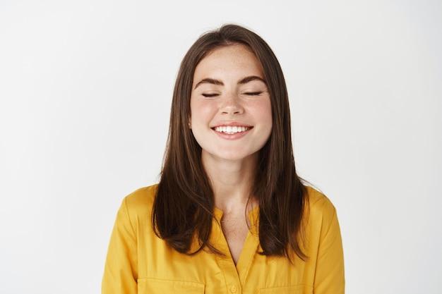 Zbliżenie szczęśliwej i zachwyconej młodej kobiety uśmiechającej się z zamkniętymi oczami, spełniającej życzenie lub śniącej, stojącej na białej ścianie
