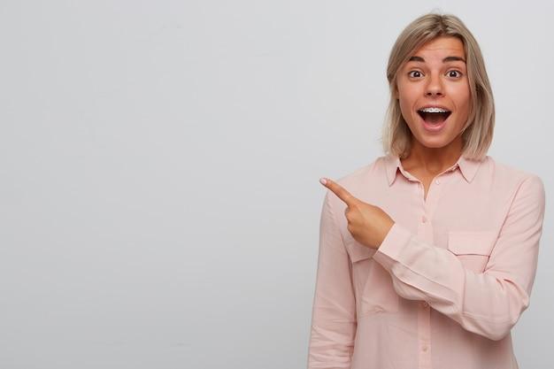 Zbliżenie szczęśliwej zdumionej blondynki młodej kobiety z szelkami na zębach i otwartymi ustami nosi różową koszulę wygląda na zaskoczoną i wskazuje na bok z palcem odizolowanym na białej ścianie