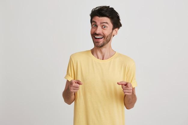 Zbliżenie szczęśliwy atrakcyjny brodaty młody człowiek nosi żółtą koszulkę, uśmiechając się i wskazuje na aparat obiema rękami na białym tle