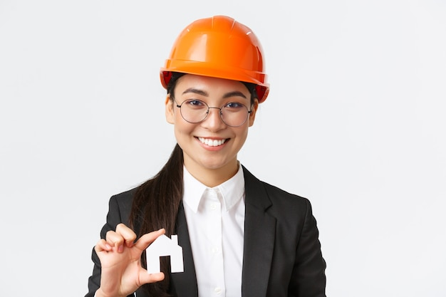 Zbliżenie: szczęśliwy azjatycki żeński inżynier, agent nieruchomości w kasku i garniturze trzyma miniaturowy dom i uśmiechnięty, architekt pracujący nad projektem renowacji, białe tło
