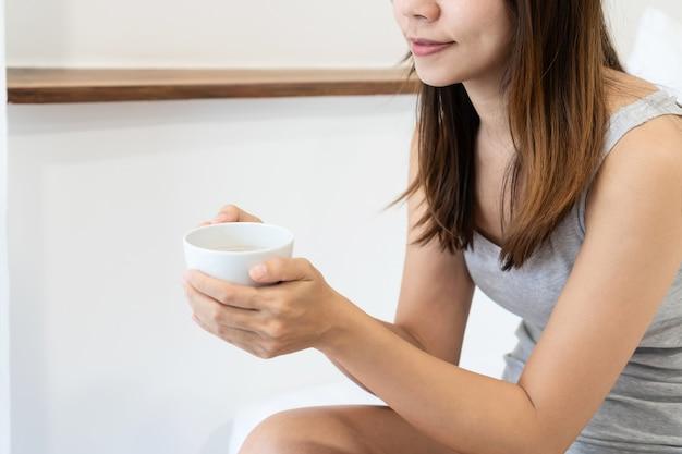 Zbliżenie szczęśliwy azjatyckie kobiety siedzącej na łóżku trzymając filiżankę kawy.