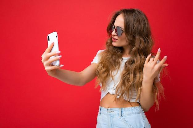 Zbliżenie szczęśliwy niesamowity piękna młoda kobieta trzymając telefon komórkowy przy użyciu selfie zdjęcie przy użyciu