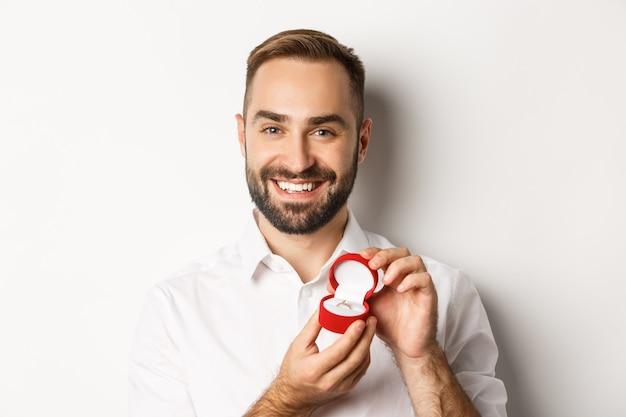Zbliżenie: szczęśliwy przystojny mężczyzna składający oświadczyny, trzymając obrączkę w pudełku i uśmiechnięty, prosząc o rękę, białe tło.