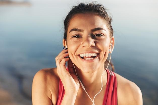 Zbliżenie szczęśliwy sportsmenka, słuchanie muzyki