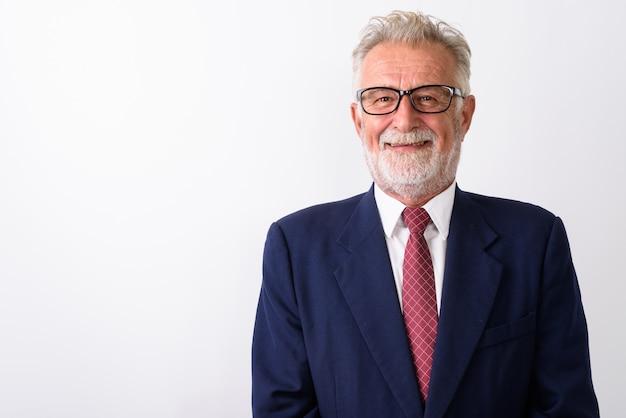Zbliżenie szczęśliwy starszy brodaty biznesmen uśmiechnięty podczas noszenia okularów na białym tle