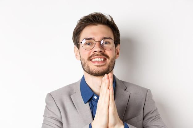 Zbliżenie szczęśliwy wdzięczny facet w okularach i garniturze okazujący wdzięczność, znak namaste i uśmiechnięty, stojący na białym tle.
