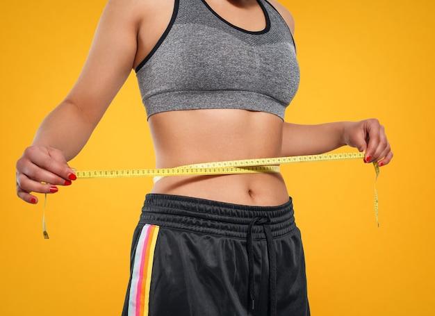 Zbliżenie szczupła kobieta pomiaru jej talii z centymetrem. na białym tle na żółtym tle.