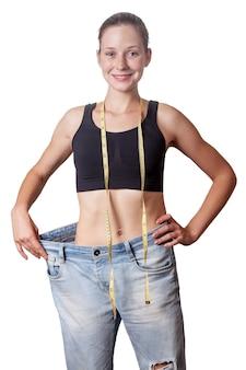 Zbliżenie szczupła talia młodej kobiety w duże dżinsy pokazujące udaną utratę wagi, na białym tle, koncepcja diety.