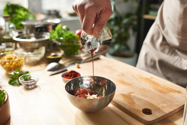 Zbliżenie: szef wlewa sos sojowy do miski on robi sałatkę jarzynową w kuchni