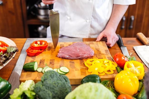Zbliżenie szefa kucharza gotowania mięsa i sałatki ze świeżymi warzywami na stole