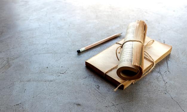 Zbliżenie szkła, ołówek i notatnik na cementowej podłoga