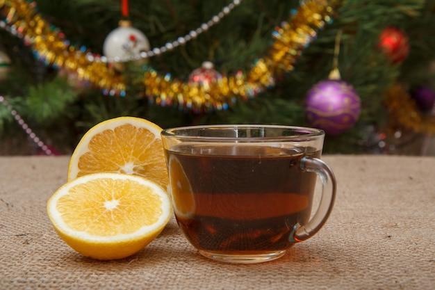 Zbliżenie szklana filiżanka herbaty i kawałki cytryny na stole z worze i choinki jodły z zabawkami kulkami i girlandami na tle.