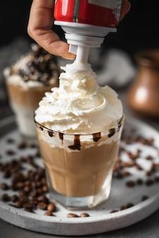 Zbliżenie szklanka kawy ze śmietaną