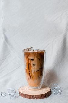 Zbliżenie szklankę mrożonej kawy z mlekiem na stole
