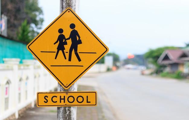 Zbliżenie szkolny znak ostrzegawczy z miękką ostrością i nadmiernym światłem w tle