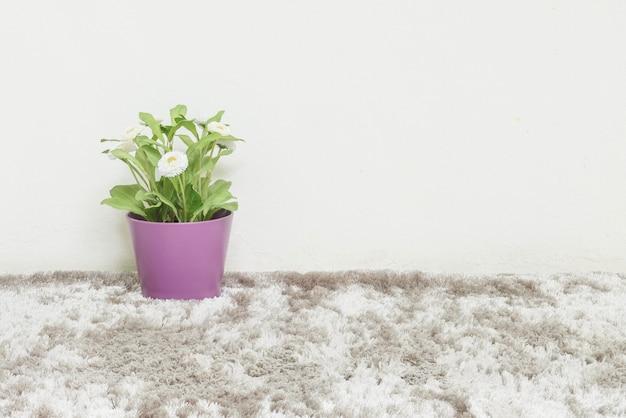 Zbliżenie sztuczne zielone rośliny wykonane z tworzywa sztucznego z białym kwiatem w fioletowy garnek na niewyraźne szary dywan