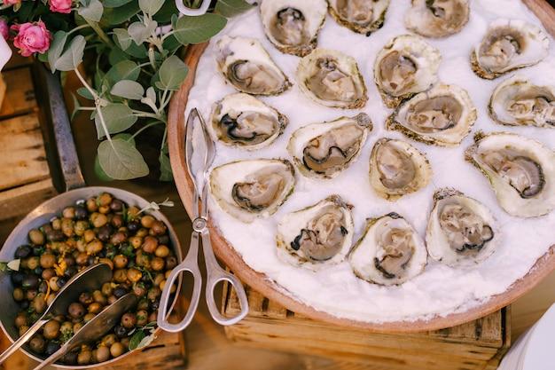 Zbliżenie szwów na talerzu na stole z szczypcami kuchennymi i chochlą nadziewanych oliwek na