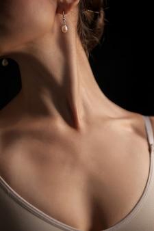 Zbliżenie: szyja młodej kobiety na ciemnym tle