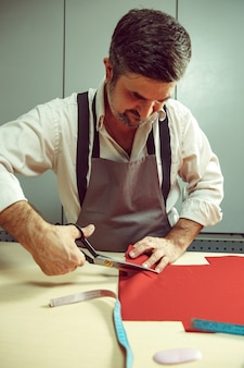 Zbliżenie tabeli krawców męskimi rękami śledzenie wzoru tkaniny na ubrania w tradycyjnym atelier studio. mężczyzna w kobiecym zawodzie. pojęcie równości płci